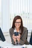 使用智能手机的愉快的女商人 免版税图库摄影
