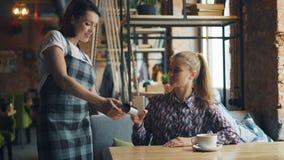 使用智能手机的愉快的少女然后支付在网上在咖啡馆使用设备 股票录像