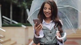 使用智能手机的愉快的年轻女商人走在多雨天气,微笑的街道上的,拿着伞 股票视频