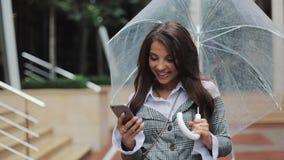 使用智能手机的愉快的年轻女商人走在多雨天气,微笑的街道上的,拿着伞 股票录像
