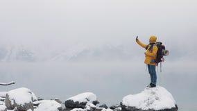 使用智能手机的愉快的旅客人在远足冬天游览 美国徒步旅行者在石头站立在山湖附近 多雪 股票录像