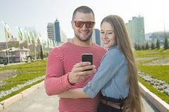 使用智能手机的愉快的男人和妇女 免版税库存照片
