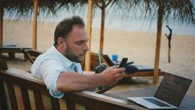 使用智能手机的成功的轻松的商人为娱乐,当工作在网上在夏天海洋手段海滩时 股票录像