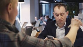 使用智能手机的成熟人和工作在办公室 股票录像