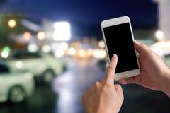 使用智能手机的手在夜城市bokeh 免版税库存照片