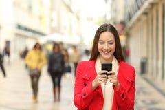 使用智能手机的时尚妇女在冬天 免版税库存照片