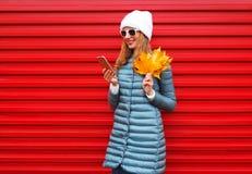 使用智能手机的时尚秋天微笑的妇女拿着黄色槭树叶子 免版税图库摄影