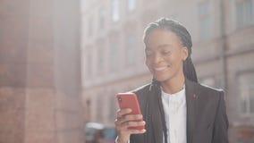 使用智能手机的时髦的非洲的女商人走在街道上的在商业中心附近 黑时髦 dreadlocks ?? 影视素材