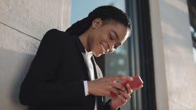 使用智能手机的时髦的非洲的女实业家站立在街道上在商业中心附近 黑时髦 dreadlocks ?? 股票录像