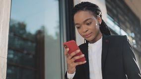 使用智能手机的时髦的非洲的女实业家站立在街道上在商业中心附近 黑时髦 dreadlocks ?? 股票视频