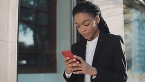 使用智能手机的时髦的非洲的女实业家站立在街道上在商业中心附近 黑时髦 dreadlocks 影视素材