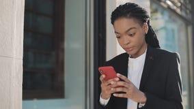 使用智能手机的时髦的非洲的女实业家站立在街道上在商业中心附近 黑时髦 dreadlocks 股票录像