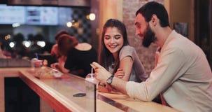 使用智能手机的有吸引力的年轻夫妇在傍晚咖啡馆 朋友,通信,夫妇,约会,闲谈 股票视频