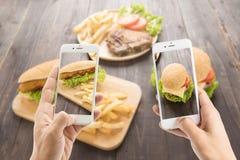 使用智能手机的朋友为热狗和hamburge照相 免版税库存照片