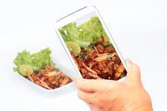 使用智能手机的朋友采取照片在烤辣味番茄酱的辣炸鸡份额的社会网络 选择聚焦 免版税图库摄影