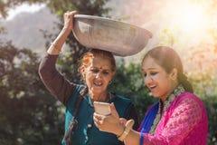 使用智能手机的母亲和女儿 免版税图库摄影