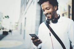 使用智能手机的特写镜头观点的愉快的微笑的非洲人室外 画象年轻黑快乐人发短信sms 库存照片