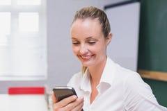 使用智能手机的白肤金发的微笑的女实业家 免版税库存图片