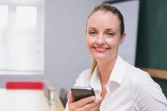 使用智能手机的白肤金发的微笑的女实业家 库存照片