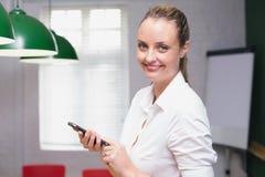 使用智能手机的白肤金发的微笑的女实业家 库存图片