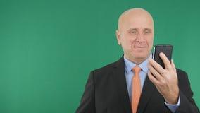 使用智能手机的确信和愉快的商人图象 库存图片