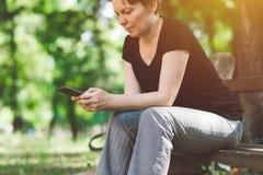 使用智能手机的社会网络上瘾者户外 免版税图库摄影