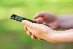 使用智能手机的社会网络上瘾者户外 图库摄影