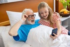 使用智能手机的祖父和孩子 库存图片