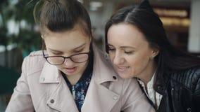 使用智能手机的秀丽青少年的女孩显示照片对她的母亲 谈论,有闲谈 ??????????? 股票录像
