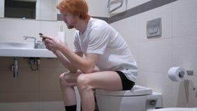 使用智能手机的红头发人人在洗手间,洗脸台 免版税库存照片
