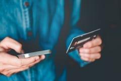 使用智能手机的网路银行商人有信用卡飞翅的 库存图片
