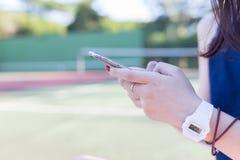 使用智能手机的美丽的亚裔女孩 免版税库存照片