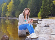 使用智能手机的美丽的少妇在湖附近 免版税库存照片