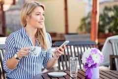 使用智能手机的美丽的年轻女人和喝咖啡在咖啡馆 免版税库存图片
