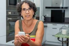 使用智能手机的美丽的成熟妇女在厨房 库存图片