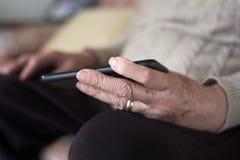 使用智能手机的老妇人 免版税库存照片