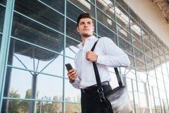 使用智能手机的英俊的商人在办公楼附近 免版税库存图片