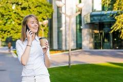 使用智能手机的观点的一个年轻可爱的女商人 库存图片