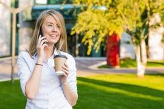 使用智能手机的观点的一个年轻可爱的女商人 免版税库存图片