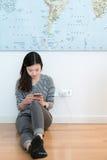 使用智能手机的逗人喜爱的亚裔女孩,当充电时 库存图片