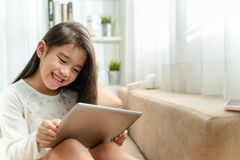 使用智能手机的逗人喜爱的孩子和微笑,当坐沙发时 库存照片