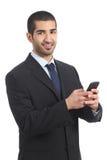 使用智能手机的阿拉伯商人和看照相机 免版税库存照片