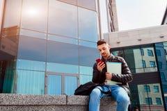 使用智能手机的阿拉伯学生外面 年轻人看在现代大厦前面的电话在类以后 免版税库存图片