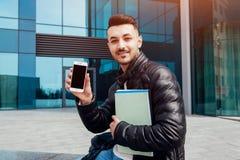 使用智能手机的阿拉伯学生外面 愉快的人在类以后显示电话和举行习字簿外面 免版税图库摄影