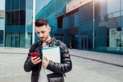 使用智能手机的阿拉伯学生外面 确信的人看在现代大厦前面的电话在类以后 库存图片