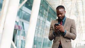 使用智能手机的非裔美国人的商人走在办公楼附近的 事务,人们,通信 影视素材