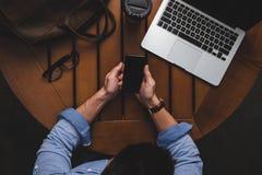 使用智能手机的顶上的观点的自由职业者在与膝上型计算机,皮包和咖啡的木桌 库存照片