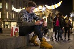 使用智能手机的年轻人在城市 库存照片