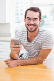 使用智能手机的年轻人,当食用咖啡时 图库摄影