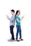 使用智能手机的年轻夫妇 免版税库存照片